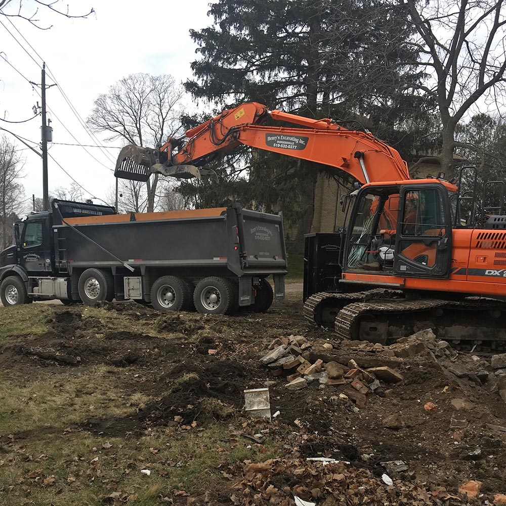 Excavating demolition site, loading into dump truck